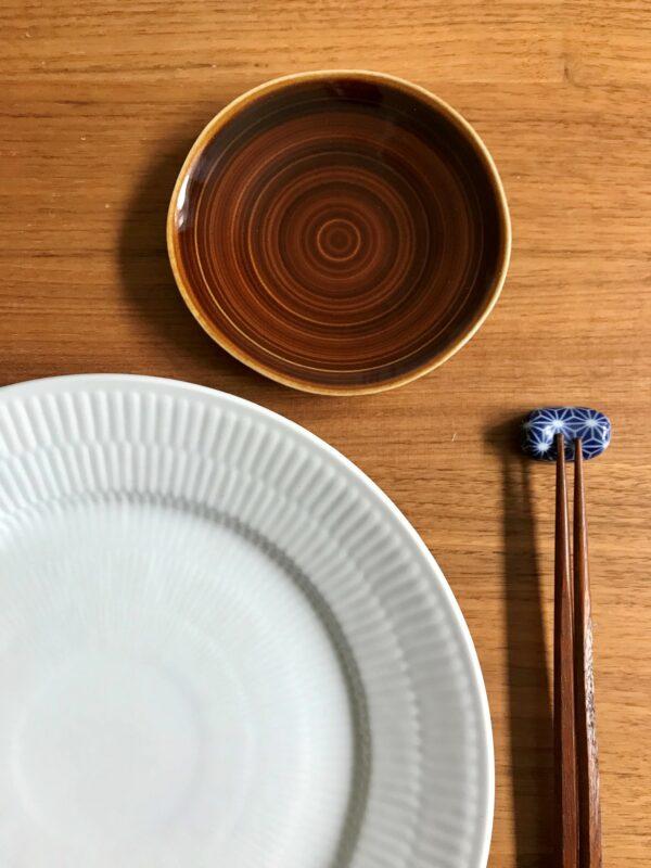 Brun soyaskål og blå spisepindeholder med mønster